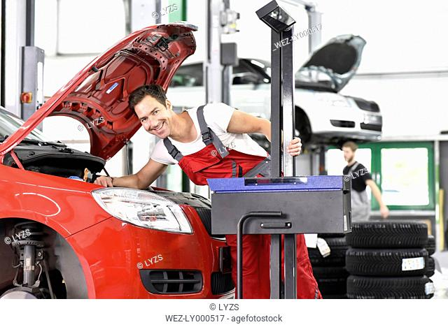 Car mechanic working in repair garage, setting car headlights