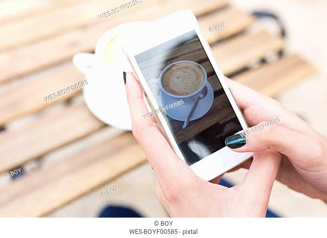 Woman taking a photo of her cappuccino with smartphone, close-up