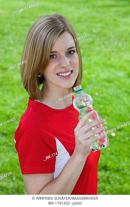 Young woman wearing sports clothing with a water bottle in hand, smiling