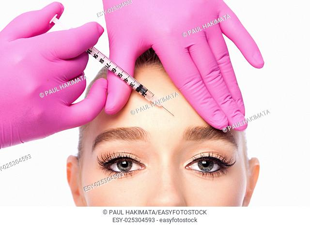 Beautiful face frown wrinkles filler collagen injection on forehead Cosmetic skincare spa beauty treatment with pink gloves by eye, on white