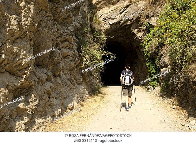 Tourist woman walking at Genil River Trail, a former railroad track, Guejar Sierra, Sierra Nevada Natural Park, province of Granada, Andalucia, Spain