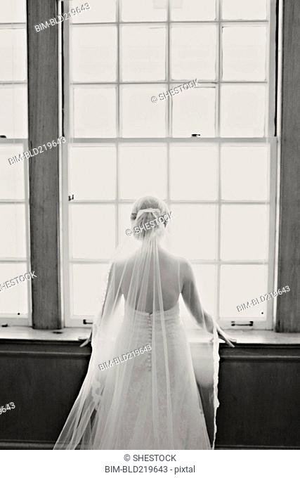 Bride in veil and wedding gown standing at window