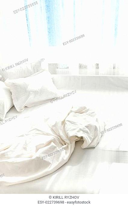 unmade bed against window