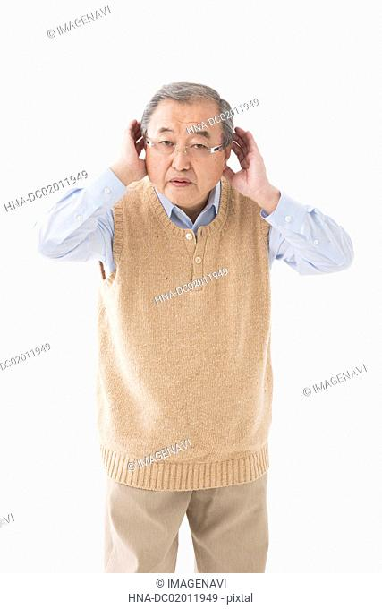 Senior man listening with hand to ear