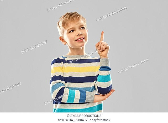 little boy in striped pullover pointing finger up