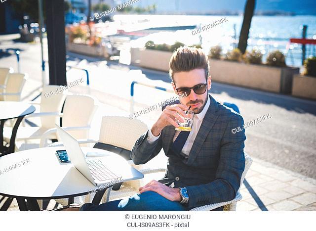 Businessman having a drink at lakeside cafe, Rovato, Brescia, Italy