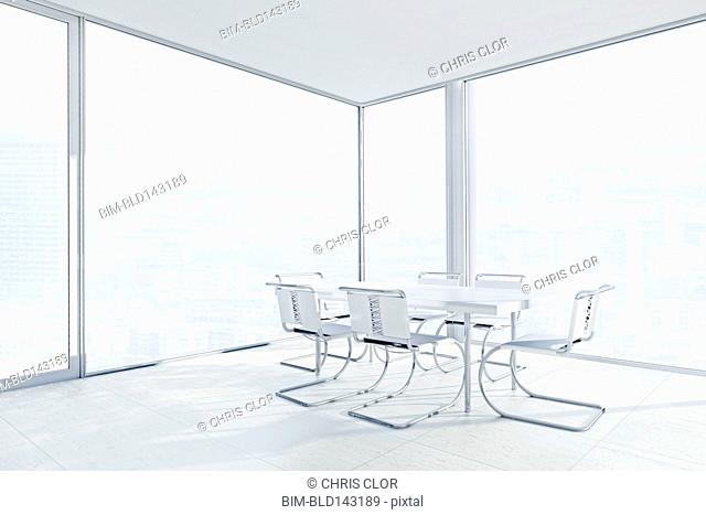 Empty chairs and conference table in office