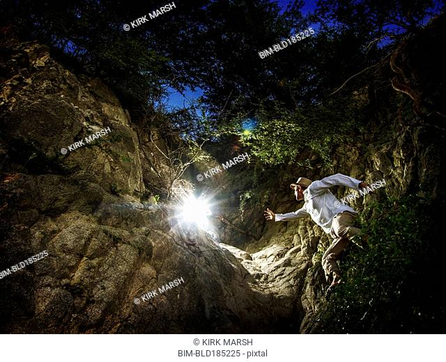 Caucasian man reaching for light in forest