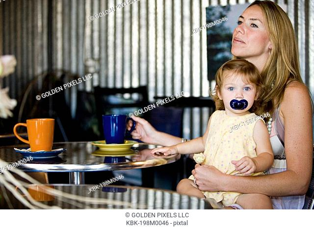 Young mother having coffee in cafi with baby on lap