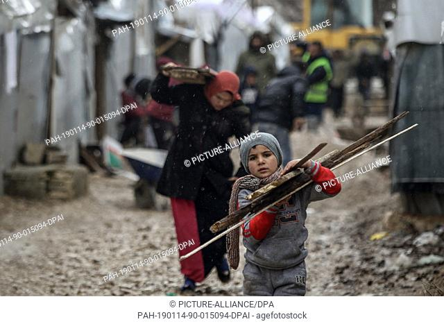 13 January 2019, Lebanon, Barelias: A Syrian refugee boy carries lodges of wood to be used to support his family·s tent from an upcoming storm as others work on...