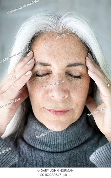 Close up of mature woman meditating with eyes closed and hands on forehead