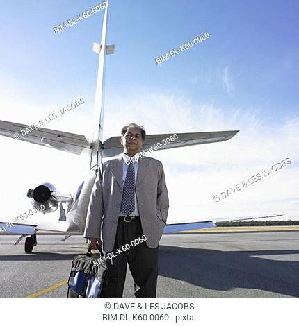 Indian businessman standing next to airplane, Perth, Australia