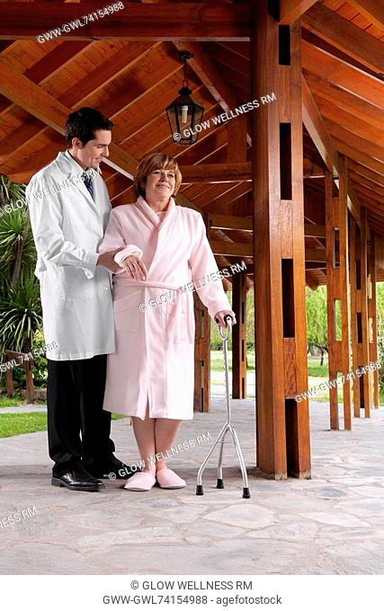 Doctor assisting a patient in walking in a rehabilitation centre