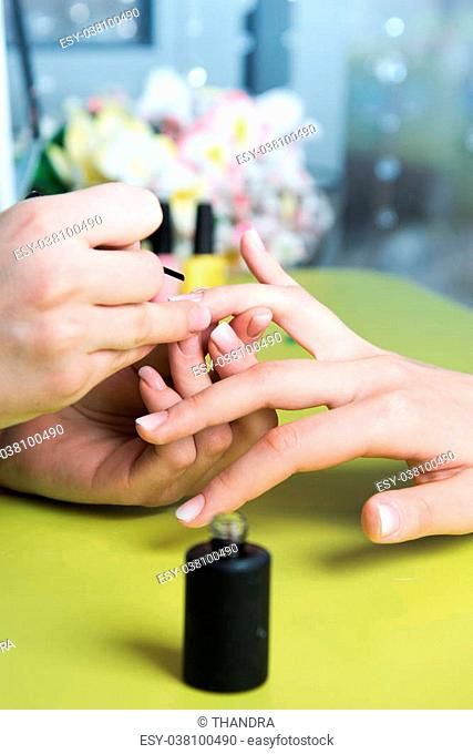 Closeup shot of a woman in a nail salon receiving a manicure by a beautician with nail file. Woman getting nail manicure