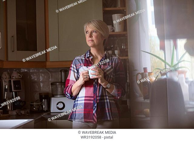 Mature woman having coffee in kitchen