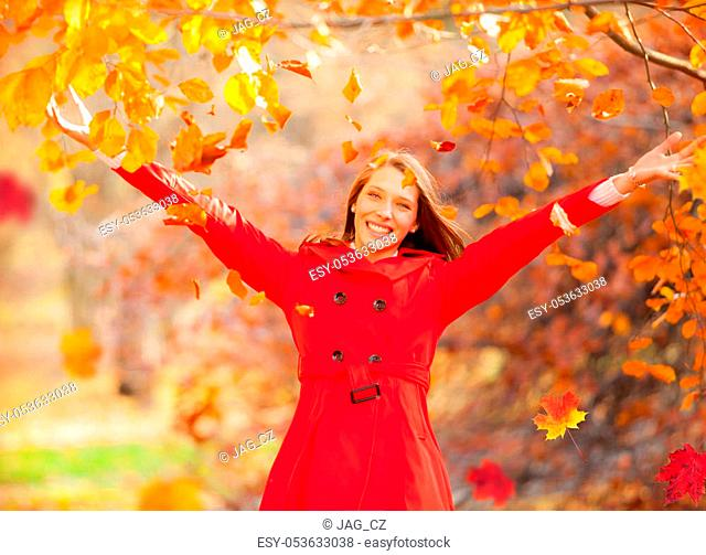 Beautiful young woman enjoying autumn nature in red jacket dress. Beauty and fashion photo, seasonal and holiday