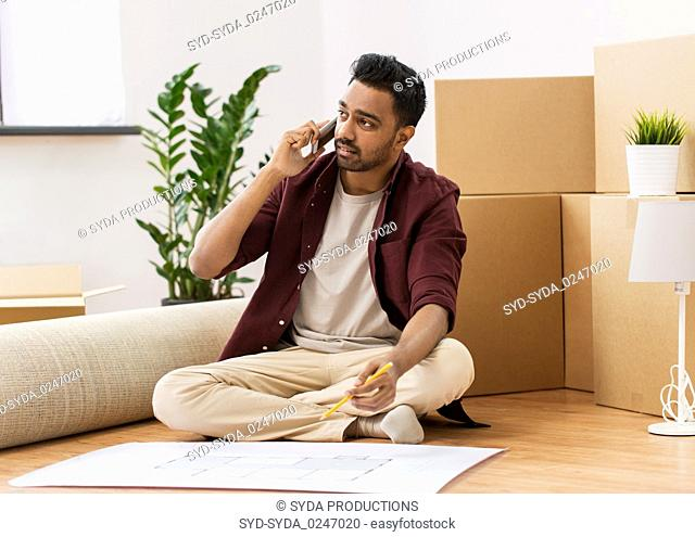 man with blueprint and boxes moving to new home