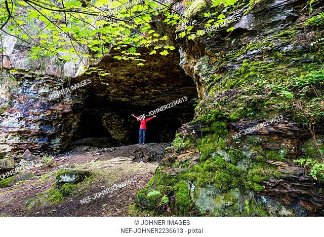 Hiker in front of cave