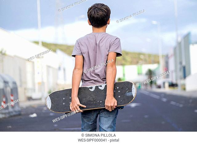 Spain, Tenerife, back view of boy holding his skateboard behind his back