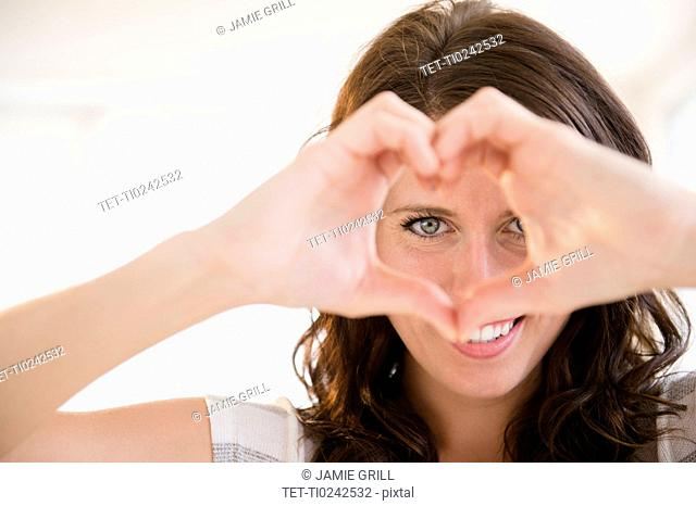 Portrait of young woman making heart shape with her hands