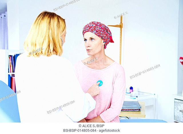 Doctor auscultating a woman suffering from cancer