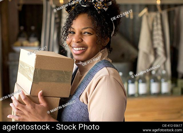 Portrait happy confident female shop owner with cardboard boxes
