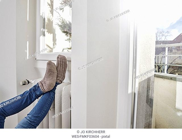 Legs of woman reating her feet on heater