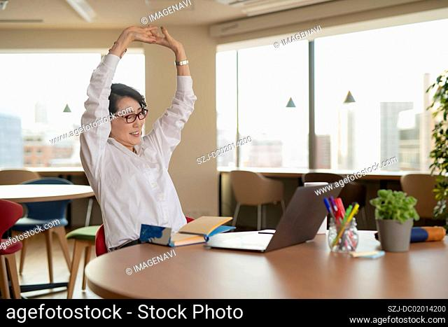 Woman stretching arms in coworking office space
