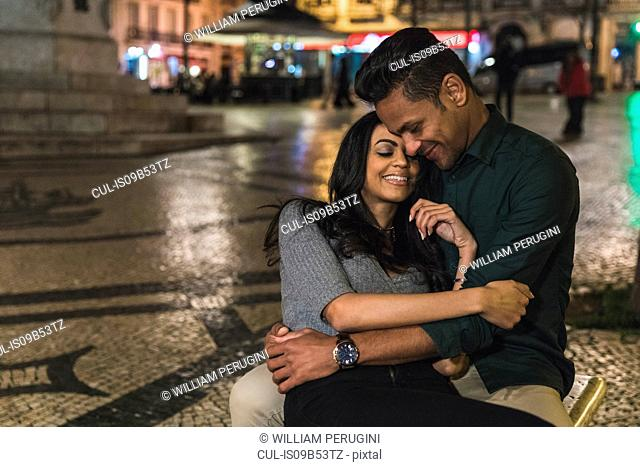 Couple in city at night, hugging, smiling, Lisbon, Portugal