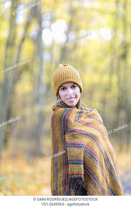 Brunette Woman in Park in Autumnn covering with a blanket smiling at camera