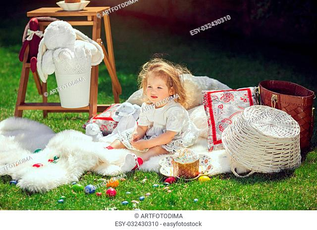 Cute little baby girl in park on green grass. Poster for Easter holiday. Selective focus on child