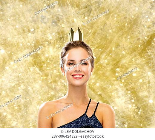 people, holidays, royalty and glamour concept - smiling woman in evening dress wearing golden crown over yellow lights background