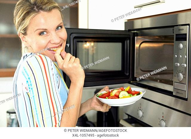 Woman in kitchen use microwave