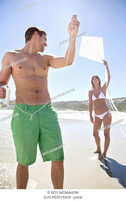 Couple flying kite on beach together