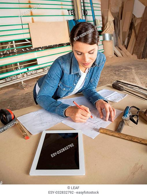 Young female carpenter working on blueprint at table in workshop