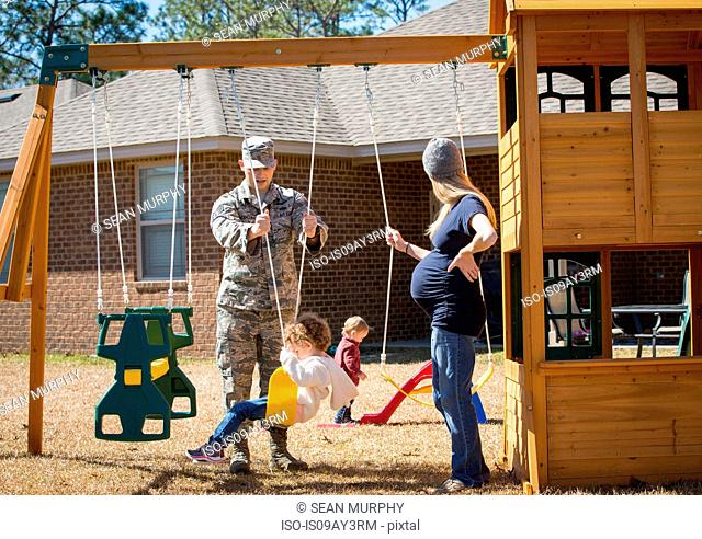 Male soldier and wife playing with daughters in garden at air force military base
