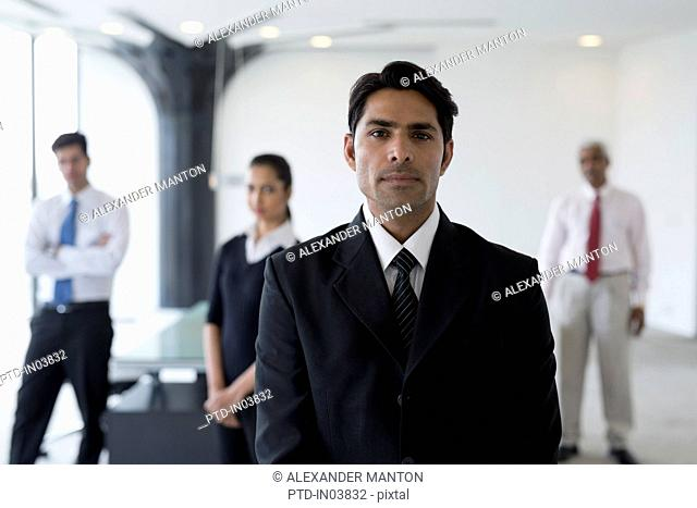 India, Business man in suit standing in front of colleagues