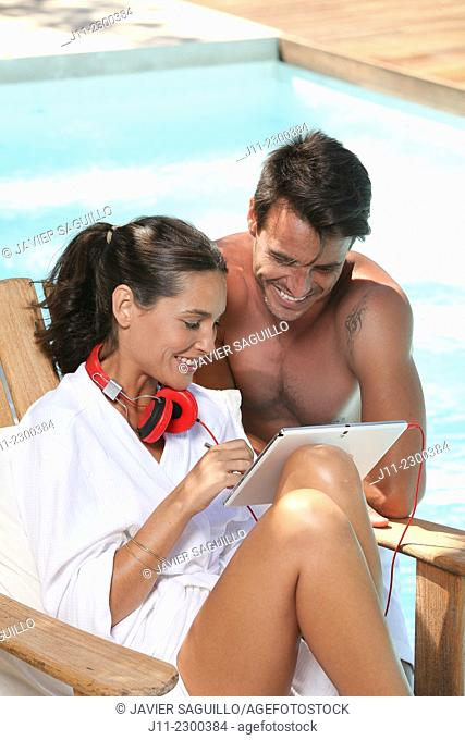 Couple, digital tablet and headphones