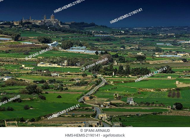 Malta, Mdina, countryside an agricultural plain dominated by a fortified city under a cloudy sky