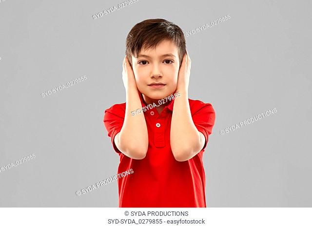 boy in red t-shirt closing ears by hands
