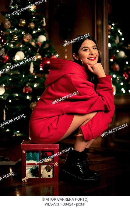 Portrait of smiling teenage girl sitting on Christmas present