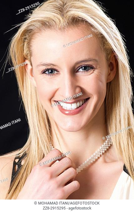 Beautiful blond woman hand pulling pearl necklace smiling