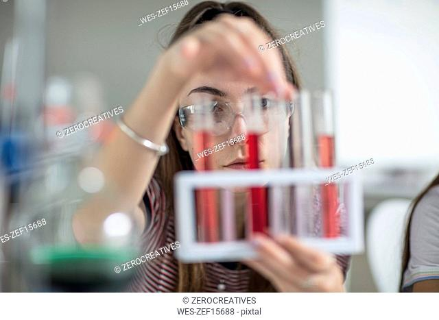 Student in science class experimenting with test tubes