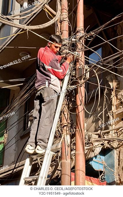 Kathmandu, Nepal. An Electrician Works on an Electrical Connection in the Center of Kathmandu. Is this a high-risk occupation? Electric wiring suggests that...