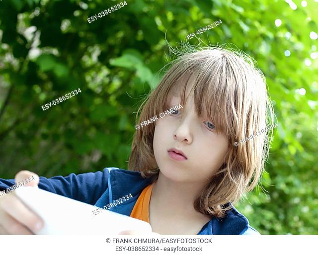 Boy with Blond Hair Reading Text Message on Mobile Phone