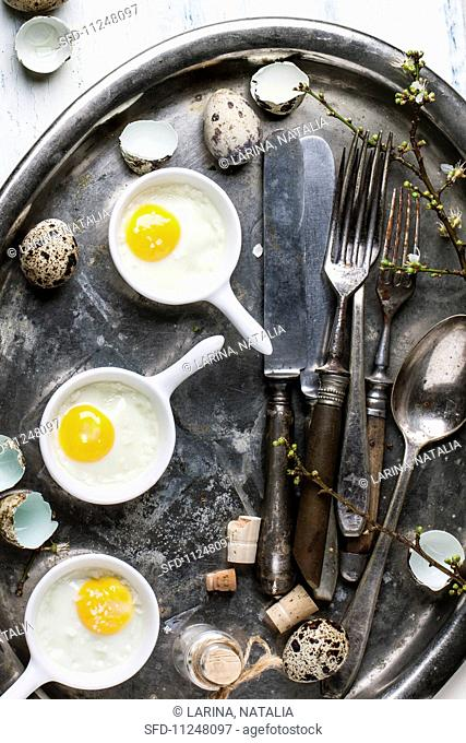 Top view on fried quail eggs with vintage tableware on old metal tray