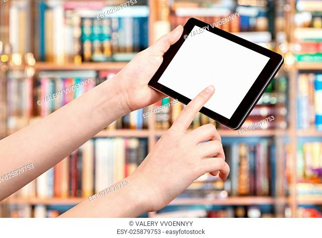 finger touches tablet pc with cut out screen in library