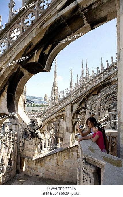 Caucasian mother and daughter photographing Milan Cathedral, Milan, Lombardy, Italy