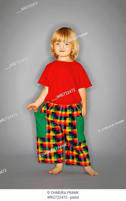boy with long blond hair standing, posing in checker pants, smiling