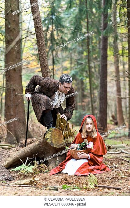 Man representing the wolf meeting girl masquerade as Red Riding Hood